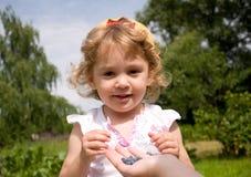 Little girl eating honeysuckle Royalty Free Stock Image