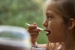 Little girl eating ice-cream. Little brother and sister eating ice-cream in a cafe outdoors Stock Photos