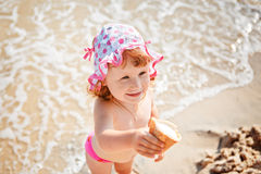 Little girl eating ice cream on beach vacation Stock Images
