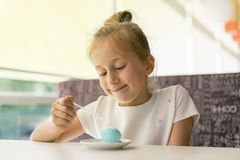 Little girl eating ice cream in a cafe. Adorable little girl eating ice cream at summer. Happy girl eating ice cream in cafe stock image