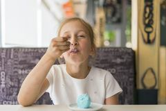 Little girl eating ice cream in a cafe. Adorable little girl eating ice cream at summer. Happy girl eating ice cream in cafe stock images