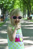 Little girl eating ice cream in city park stock photography