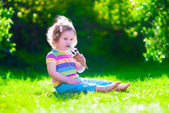 Little girl eating ice cream in the garden Royalty Free Stock Image