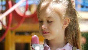 Little girl eating ice cream on a hot summer day at playground in park. stock footage