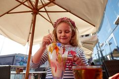 Little girl eating ice cream in outdoor cafe. Little girl eating ice cream in outdoor cafe royalty free stock photography