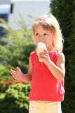 Little girl eating ice cream outdoors Stock Images