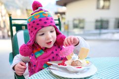 Little girl eating ice cream in outdoors cafe Stock Photography