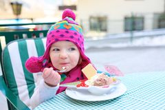 Little girl eating ice cream in outdoors cafe Royalty Free Stock Photography