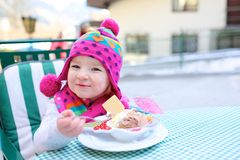 Little girl eating ice cream in outdoors cafe Stock Photo