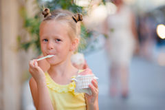 Little girl eating ice-cream outdoors at summer. Cute kid enjoying real italian gelato near Gelateria in Rome Stock Images