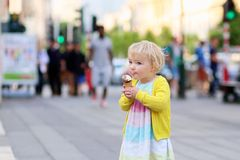 Little girl eating ice cream walking in the city Royalty Free Stock Image