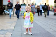 Little girl eating ice cream walking in the city Royalty Free Stock Photo
