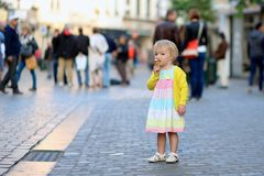 Little girl eating ice cream walking in the city Royalty Free Stock Photos