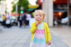 Little girl eating ice cream walking in the city Stock Photo