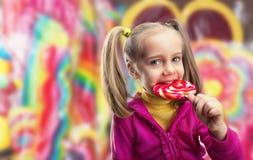 Little girl eating lollipop Stock Photos