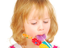 Little girl eating  lollipops  isolated Stock Photo