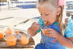 Little girl eating a lot of orange ice cream in a street cafe royalty free stock images
