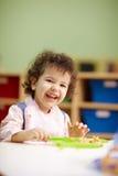 Little girl eating lunch in kindergarten stock photo