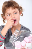 Little girl eating marshmallows. A little girl eating marshmallows Royalty Free Stock Photo