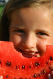 Little girl eating melon Stock Images