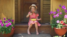 Cute Little Girl Eating Strawberry in Summer Day. Little Girl Eating Natural Berries Outdoors in Summer Day. Cute Young Girl Holding a Bowl Full of Fresh stock video footage