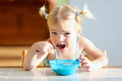 Little girl eating oatmeal for breakfast Stock Photography