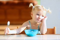Little girl eating oatmeal for breakfast Stock Images