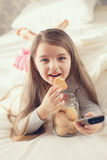 The little girl is eating oatmeal cookies in bed Stock Image