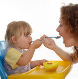 Little girl eating from one pot with woman Stock Photography