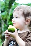 Little Girl Eating an Orange Stock Image