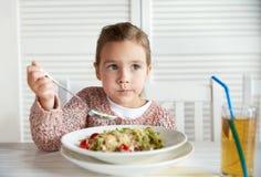 Little girl eating pasta for dinner at restaurant Stock Photos
