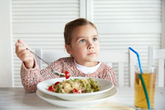 Little girl eating pasta for dinner at restaurant Stock Images