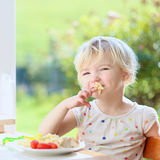 Little girl eating pasta for lunch Stock Image