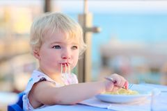 Little girl eating pasta at restaurant Royalty Free Stock Photo