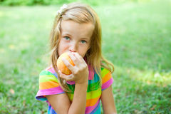 Little girl eating peach. In the park Royalty Free Stock Photos