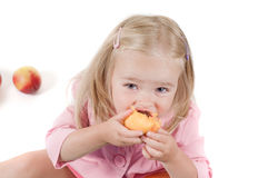 Little girl eating peach in studio Stock Image