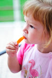 Little girl eating a piece of carrot Stock Images