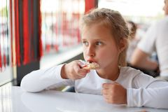 Little girl eating a pizza in cafe. Little girl eating a pizza with closed eyes in cafe. Horizontal photo Stock Photography