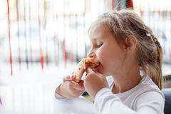 Little girl eating a pizza in cafe. Little girl eating a pizza with closed eyes in cafe. Horizontal photo Royalty Free Stock Photography