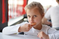 Little girl eating a pizza in cafe. Little girl eating a pizza with closed eyes in cafe. Horizontal photo Stock Image