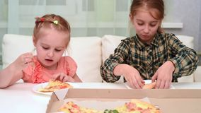 Little girl eating pizza and her older sister waving her hand stock footage