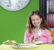 Little girl eating pizza Stock Photos