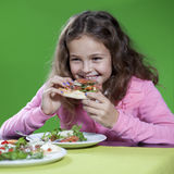 Little girl eating pizza stock photos