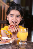 Little girl eating a pizza slice. Little girl in east indian clothes holding a pizza slice stock photography