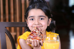 Little girl eating a pizza slice. Little girl in east indian clothes holding a pizza slice royalty free stock photography