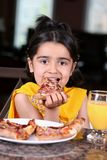 Little girl eating a pizza slice royalty free stock photos