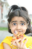 Little girl eating a pizza slice royalty free stock photography