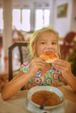 Little girl eating pizza and soup Royalty Free Stock Photography