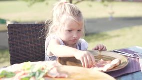 Little girl eating pizza at a table in a summer cafe stock video footage