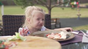 Little girl eating pizza at a table in a summer cafe stock video